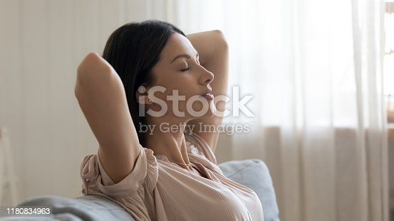 Calm young woman with closed eyes and hands behind head relaxing on couch close up, lazy day weekend at home, satisfied girl leaning back, stretching on sofa, daydreaming and meditating