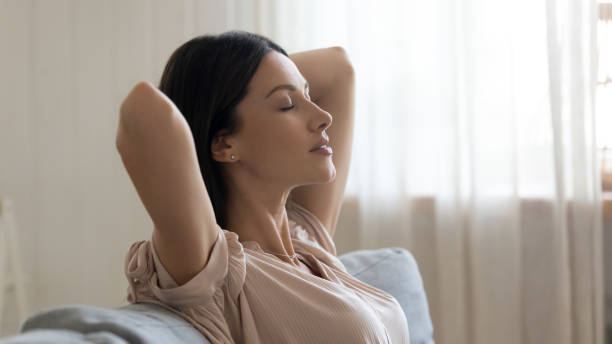 Calm young woman with closed eyes relaxing on couch Calm young woman with closed eyes and hands behind head relaxing on couch close up, lazy day weekend at home, satisfied girl leaning back, stretching on sofa, daydreaming and meditating effortless stock pictures, royalty-free photos & images
