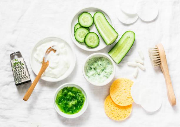 kalmerende komkommer yoghurt masker. ingrediënten voor de huisgemaakte komkommer gezicht masker-komkommer, natuurlijke yoghurt, probiotische capsule, sponzen, borstel op witte achtergrond, bovenaanzicht. plat leggen - spoorelement stockfoto's en -beelden