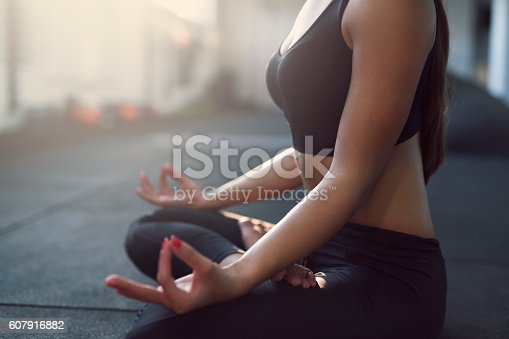 Unrecognizable young girl doing lotus yoga pose on the floor