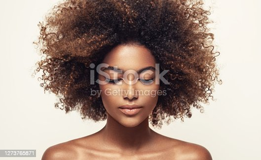 Calmness and inner concentration on the face of young beautiful woman. Natural, dense afro hair on the head brown skinned model. Girl with vibrant, melanin-rich skin tone. Beauty of youth.