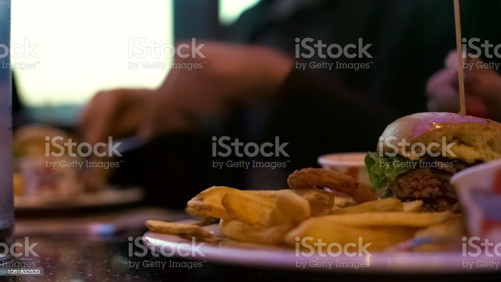 Calorie burger with french fries, people eating at cafe table,...
