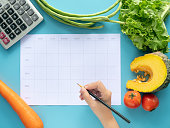 istock Calories control, meal plan, food diet and weight loss concept. top view of hand filling meal plan on blank paper with calculator and vegetable isolated on blue background 1164104489
