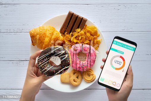 Calories counting and food control concept. woman using Calorie counter application on her smartphone with doughnut in hand and snack , cookies on plate at background