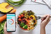istock Calories counting , diet , food control and weight loss concept. Calorie counter application on smartphone screen at dining table with salad, fruit juice, bread and fresh vegetable. healthy eating 1259984250