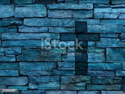 A multi colored blue rustic layered brick wall with dark inset brick Christian cross off-center. The colors on the brick wall include blue, purple, green and pink