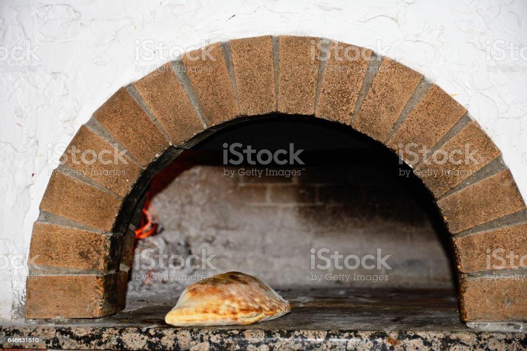 Calzone in a pizza oven, Crete. stock photo