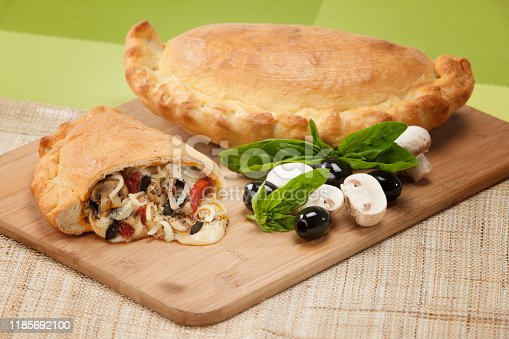 Calzone stuffed with mozzarella, basil, cheese, tomato, mushrooms and black olives.