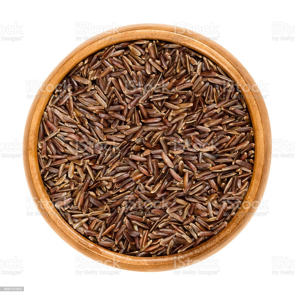 Camargue red rice grains in wooden bowl stock photo