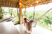 Woman admiring tropical nature and rice paddies from a hammock on vacation in Bali, Indonesia
