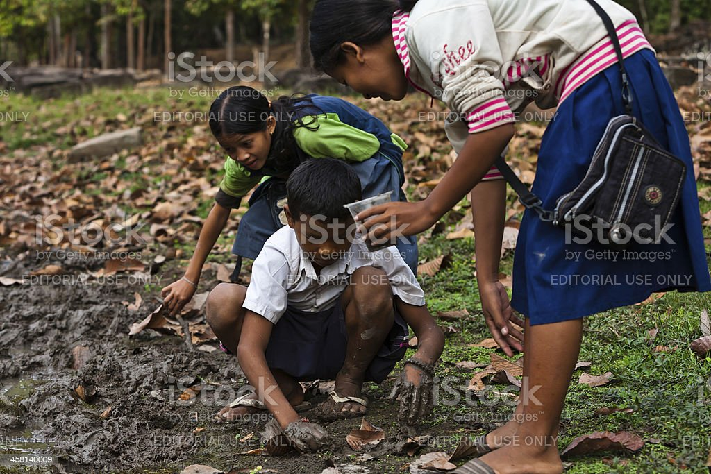 Cambodian children dig in mud for worms on lake edge royalty-free stock photo