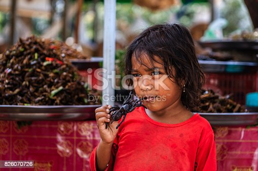 istock Cambodian little girl eating deep fried tarantula, street market, Cambodia 826070726