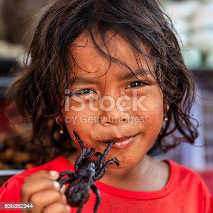 istock Cambodian little girl eating deep fried tarantula, street market, Cambodia 835382944