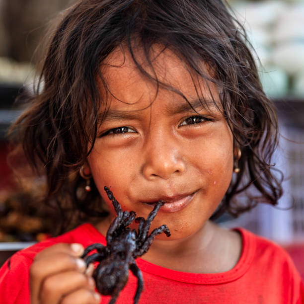 Camboya poco chica comiendo profunda frito tarantula, mercadillo, Camboya - foto de stock