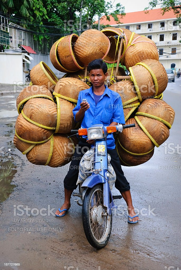Cell phone and large load on motorbike in Phnom Penh royalty-free stock photo