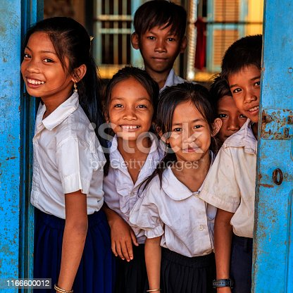 Cambodian school children standing in doorway of classroom in small village near Tonle Sap, Cambodia.