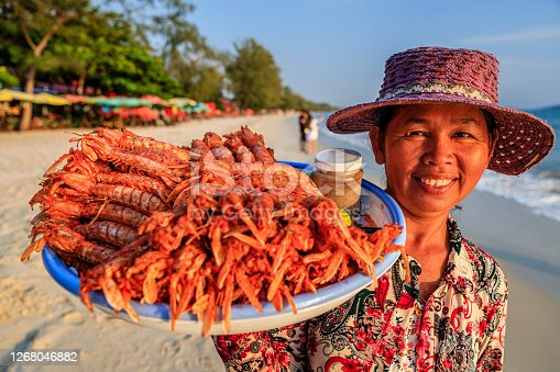 Happy Cambodian woman selling fresh lobsters on the beach, Sihanoukville, Cambodia