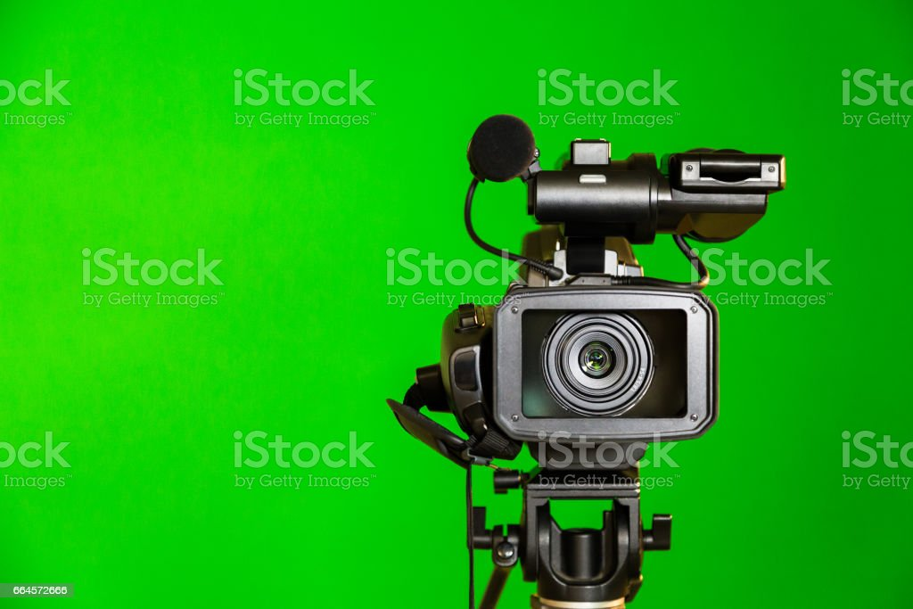 Camcorder on a green background. Filming in the interior. The chroma key stock photo