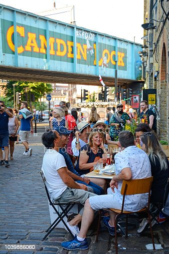 London, United Kingdom - July 7th, 2018: People spending Saturday in Camden, late afternoon. In te foregrounf on the right group of friends sitting in a outdoor pub, withe beer. In the foreground and on the left many people walking on the street.