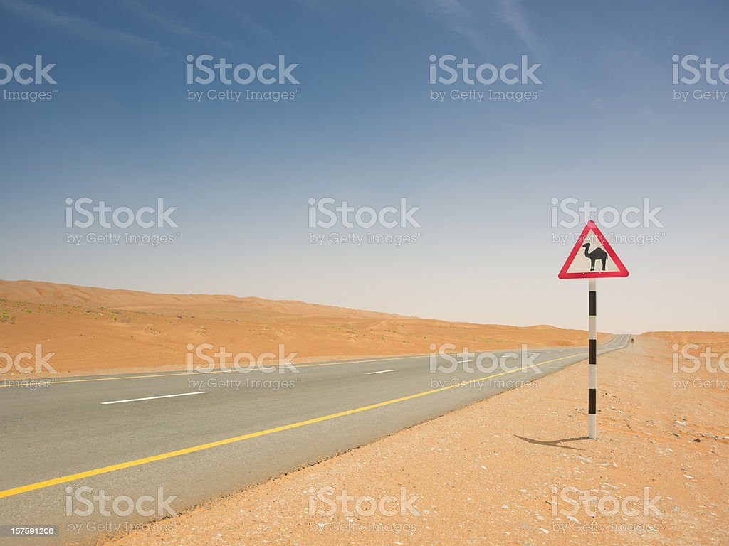 Camel Crossing Sign Empty Desert Highway stock photo