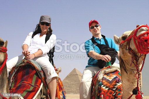 883177796 istock photo Camel in dessert 2 people riding them trip 1203034014