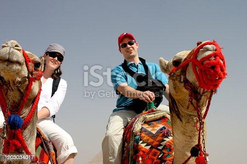 883177796 istock photo Camel in dessert 2 people riding trip 1203034017