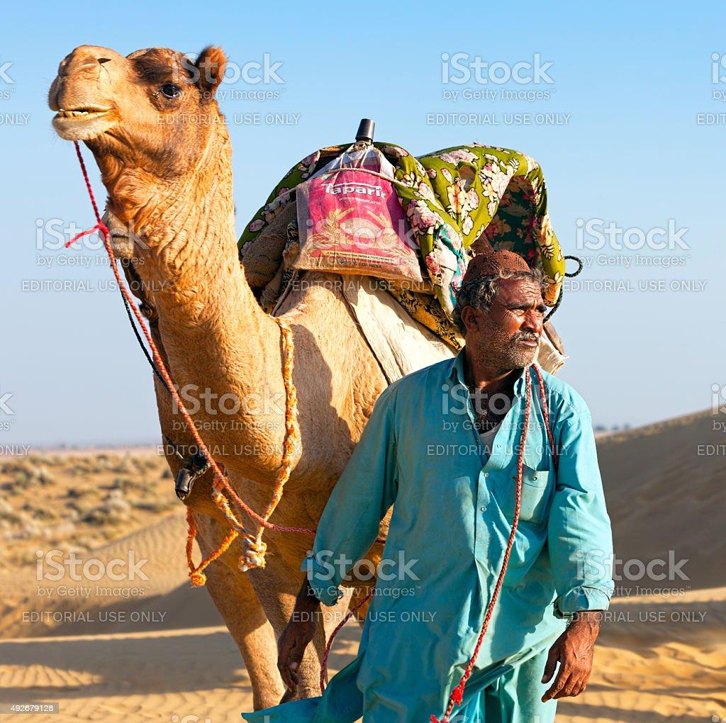 Camel man leads his camel across the Thar desert stock photo
