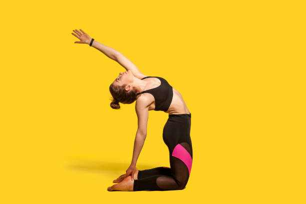 Camel pose. Athletic woman with hair bun in tight sportswear practicing yoga, doing spinal back exercise Camel pose. Athletic woman with hair bun in tight sportswear practicing yoga, doing spinal back bending ustrasana exercise with raised hand, stretching muscles. full length studio shot, sport workouts yogi stock pictures, royalty-free photos & images