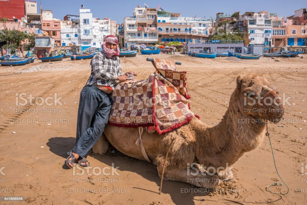 Jinete de camello en la playa de Taghazout - foto de stock