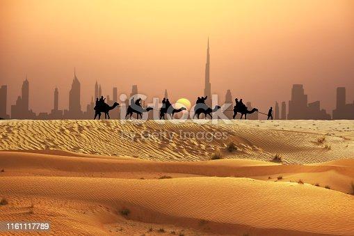 Camel tourists caravan walking on sunset desert near Dubai skyline
