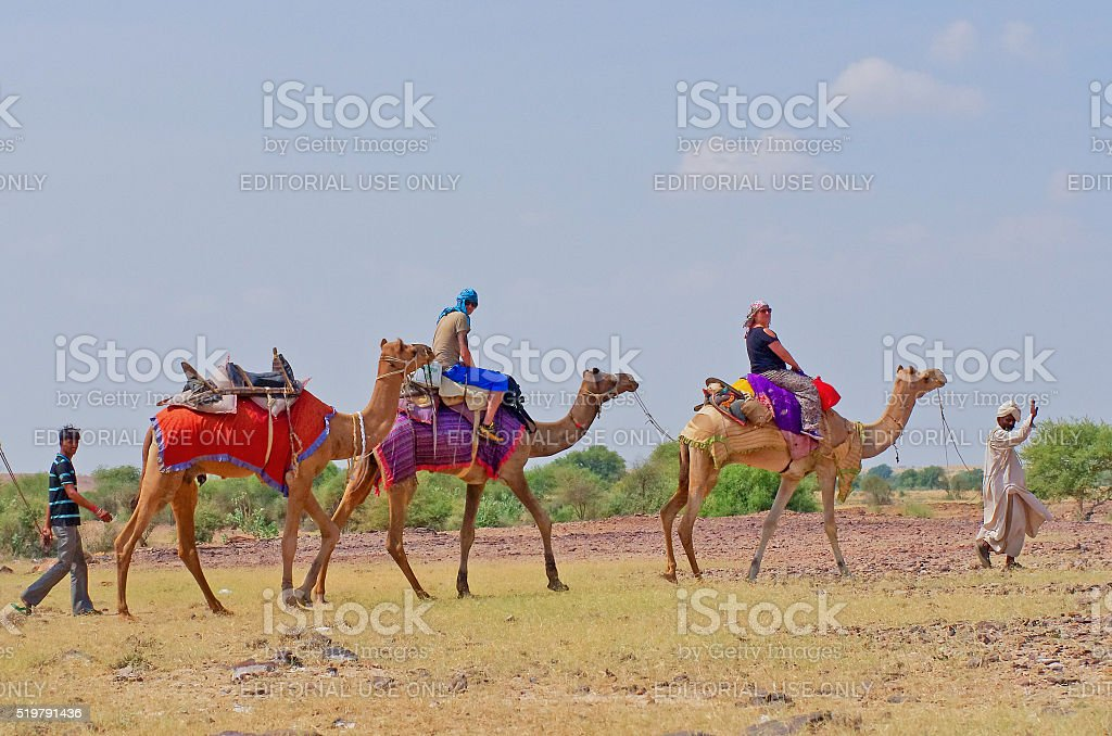 Cameleer and tourists in desert  in Jaisalmer, India. stock photo