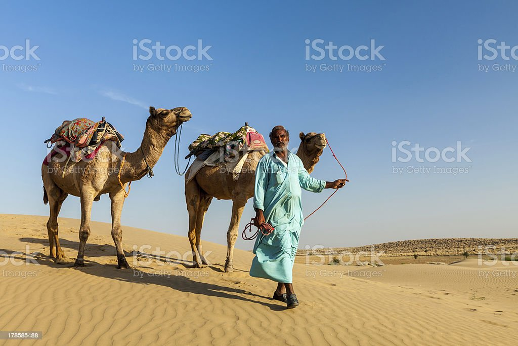 Cameleer (camel driver) with camels in dunes of Rajasthan stock photo
