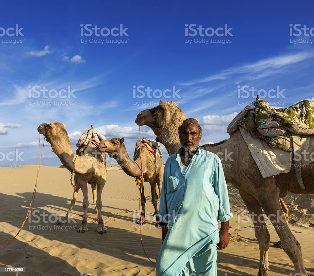 Cameleer  with camels in dunes of Thar desert. Raj royalty-free stock photo