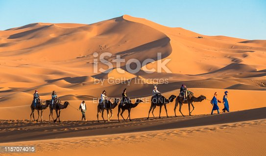 Merzouga / Morocco - March 26th, 2018: A touristic caravan of camels at the Erg Chebbi dunes in the Sahara at sunset