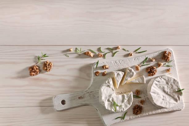 Camembert, queijo do Brie e nozes no fundo de madeira branco - foto de acervo