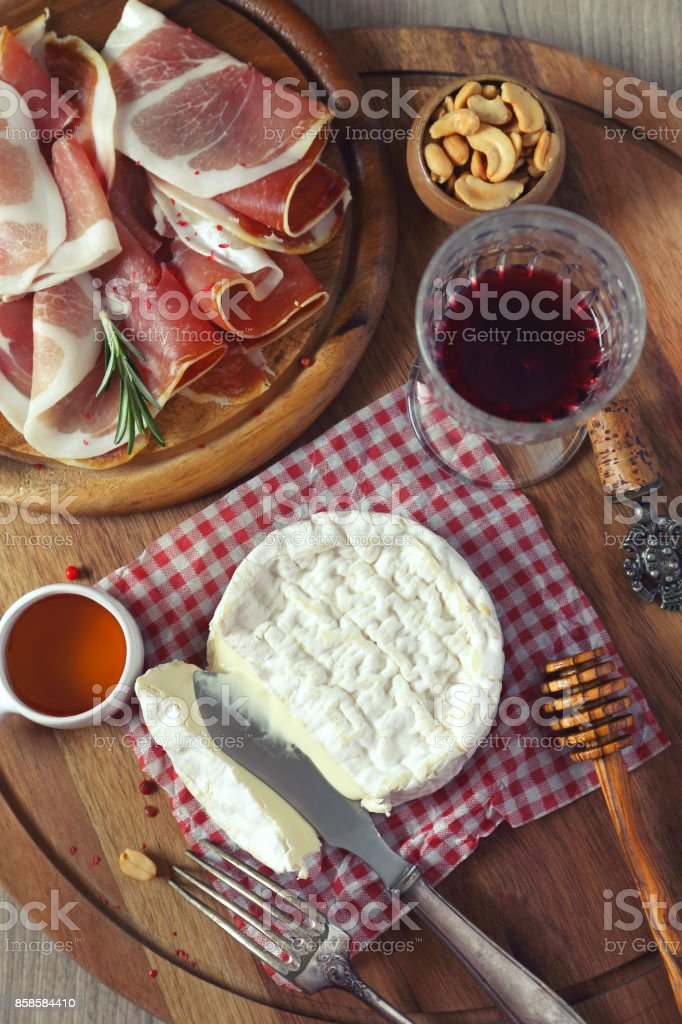 Camembert cheese, cold cuts and glass of red wine stock photo