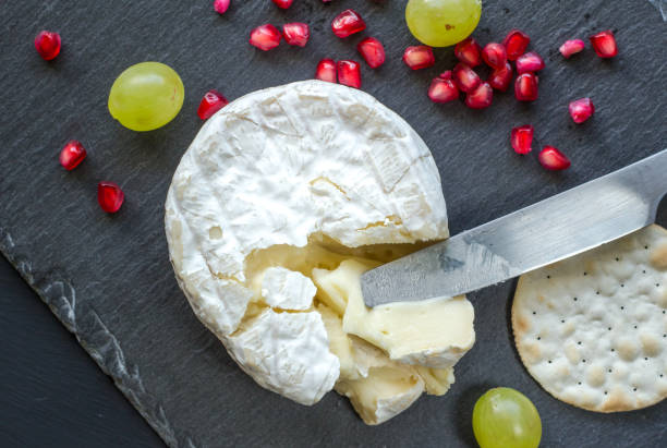 camembert cheese, knife, cracker and pomegranate seeds on cheese slate board - baked brie stock photos and pictures