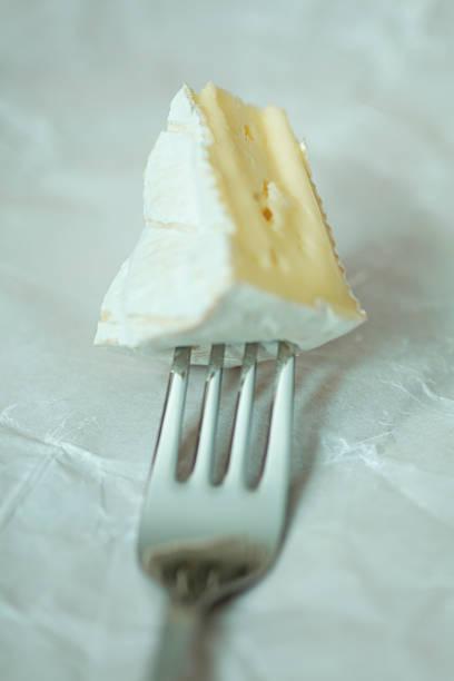 Camembert-Käse auf einer Gabel. – Foto