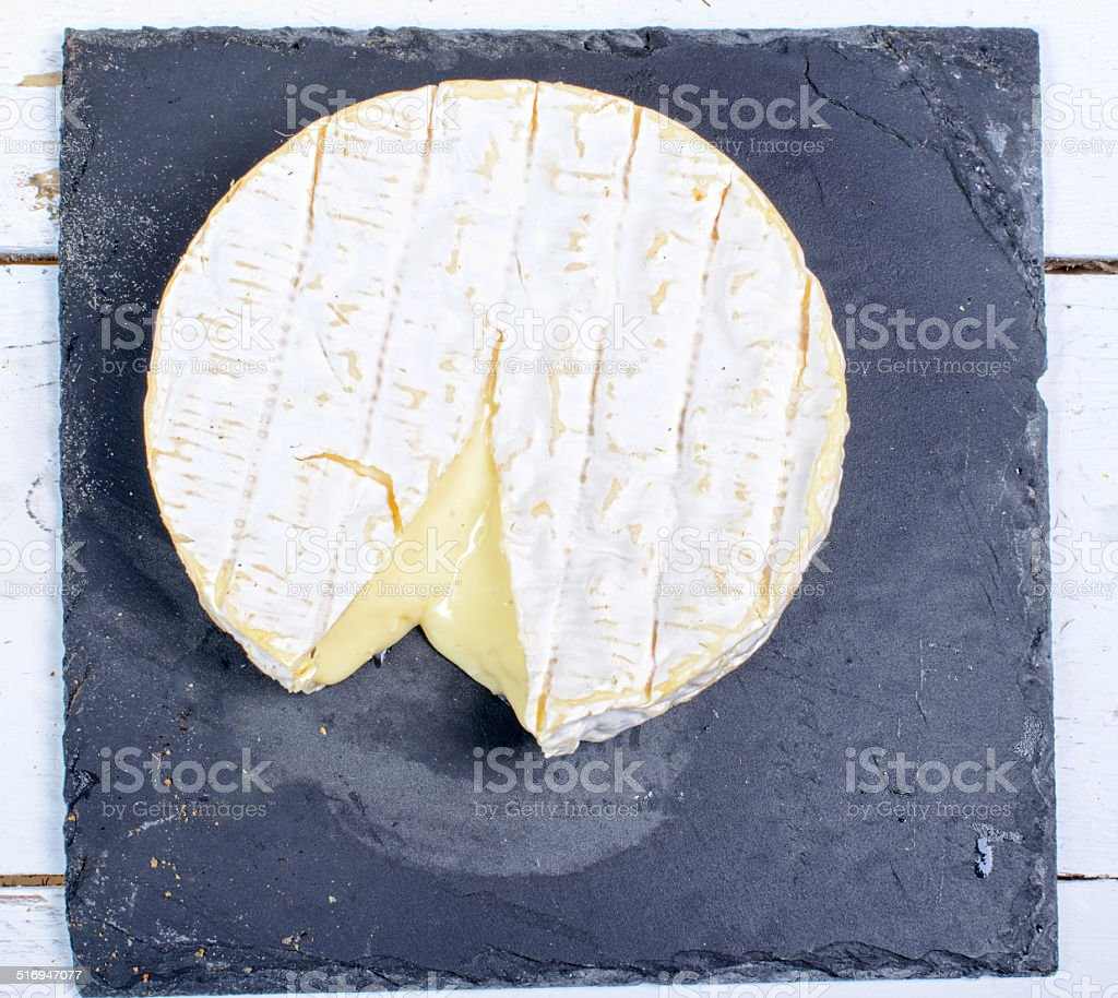 Camembert cheese on a plate slate stock photo