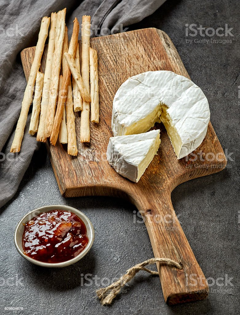 camembert cheese on wooden cutting board stock photo