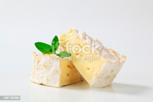 two triangular pieces of a ripe camembert cheese with green leaves of a basil