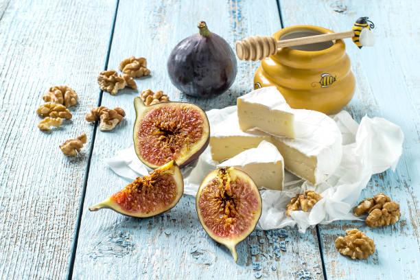 camembert käse, reife feigen, honig und walnüssen - dinge die zusammenpassen stock-fotos und bilder