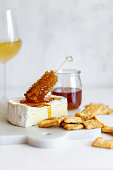 istock Camembert cheese, white wine honey and snack on white marble background 1251668173