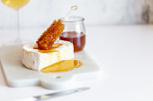istock Camembert cheese, white wine honey and snack on white marble background 1251668218