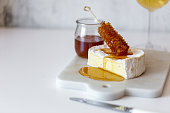 istock Camembert cheese, white wine honey and snack on white marble background 1251668235