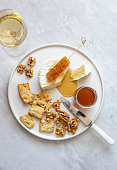 istock Camembert cheese, white wine honey and snack on white marble background 1252597648