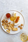 istock Camembert cheese, white wine honey and snack on white marble background 1252597669