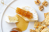 istock Camembert cheese, white wine honey and snack on white marble background 1252597687