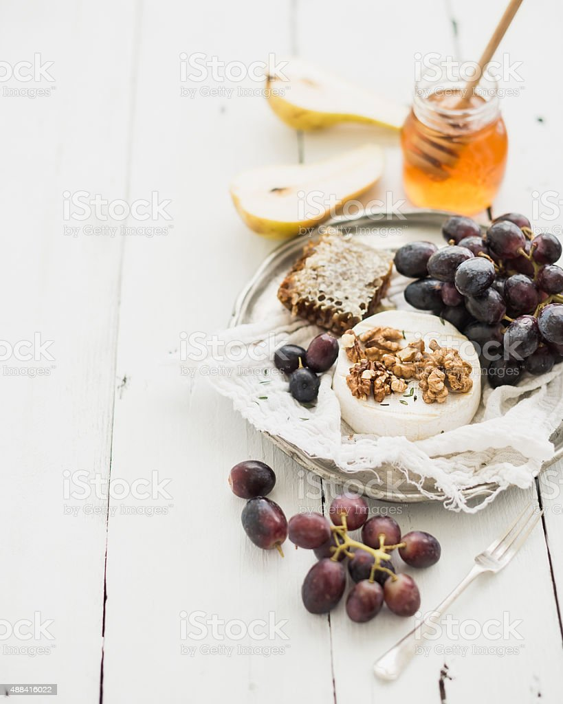 Camembert cheese with grape, walnuts, pear and honey on vintage stock photo