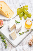 istock Camembert or brie cheese on white wooden serving board 1033053814